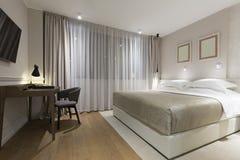 一间豪华旅馆卧室的内部在晚上 免版税库存照片