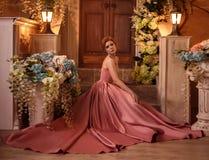 一件豪华桃红色礼服的美丽的妇女 免版税库存图片