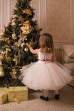 一件豪华礼服的一个小女孩装饰圣诞树 免版税库存照片