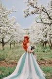 一件豪华礼服的少妇在一个开花的庭院里站立 免版税库存图片