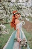 一件豪华礼服的少妇是站立和微笑在一个开花的庭院里 免版税库存照片