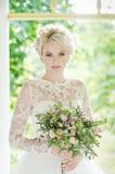 一件豪华礼服的美丽的白肤金发的新娘与 免版税库存照片