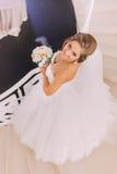 一件豪华礼服的美丽的迷人的新娘有查寻的花束的,顶视图 免版税库存图片