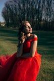 一件豪华红色礼服的美丽的妇女有一列长的火车的 图库摄影