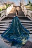 一件豪华蓝色礼服的美丽的妇女有一列长的火车的 库存图片