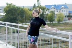 一件超短裙的性感的女孩在桥梁,铁路轨道 库存图片