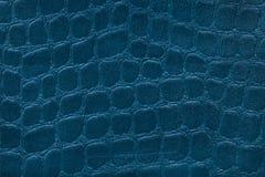 从一份软的室内装饰品纺织材料的蓝色背景,特写镜头 与样式仿效鳄鱼皮肤的织品 免版税图库摄影
