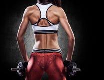 一件运动服的健身性感的妇女在加大肌肉的训练 库存图片