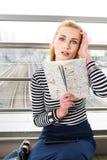 一件镶边夹克的旅游女孩金发碧眼的女人坐拿着地图和拿着他的从强的惊奇的头 免版税库存图片
