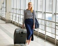 一件镶边夹克的旅游白肤金发的妇女来带着手提箱在火车站或终端 女孩拉扯行李 免版税库存照片