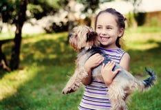 一件镶边毛线衣的小女孩微笑并且拿着一条小狗 免版税图库摄影