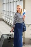 一件镶边毛线衣的旅游白肤金发的在驻地或终端的妇女有手提箱和护照的和票 图库摄影