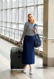 一件镶边毛线衣的旅游白肤金发的在驻地或终端的妇女有手提箱和护照的和票 库存照片