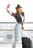 一件镶边毛线衣的旅游白肤金发的女孩带着站立在火车站的手提箱和做selfie 免版税库存图片