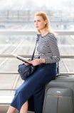 一件镶边毛线衣的旅游白肤金发的女孩有背包的坐手提箱在火车站和举行地图 库存照片