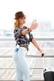 一件镶边毛线衣的旅游白肤金发的妇女有手提箱和护照的在驻地或终端做selfie 免版税库存照片