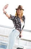 一件镶边毛线衣的旅游白肤金发的妇女有手提箱和护照的在驻地或终端做selfie 图库摄影