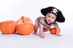 一件镶边T恤杉和一个海盗帽子的美丽的婴孩在白色 免版税库存照片