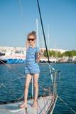 一件镶边T恤杉和太阳镜的美丽的苗条小女孩豪华小船 免版税库存图片