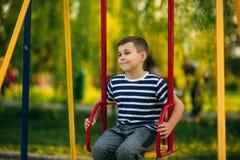 一件镶边T恤杉的一个小男孩在操场,在摇摆的摇摆使用 春天,晴朗的天气 免版税库存图片