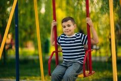 一件镶边T恤杉的一个小男孩在操场,在摇摆的摇摆使用 春天,晴朗的天气 免版税图库摄影