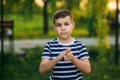 一件镶边T恤杉的一个小男孩在操场,在摇摆的摇摆使用 春天,晴朗的天气 免版税库存照片