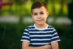 一件镶边T恤杉的一个小男孩在操场,在摇摆的摇摆使用 春天,晴朗的天气 库存图片