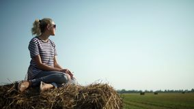 一件镶边T恤杉的年轻时髦的女孩坐干草堆 免版税库存照片