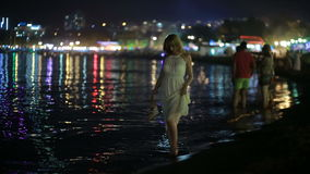 一件长的白色礼服的女孩 沿海滩的步行在晚上 股票录像