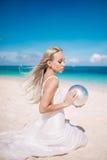 一件长的白色礼服的白肤金发的长的头发新娘坐与珍珠的白色沙子海滩 库存照片