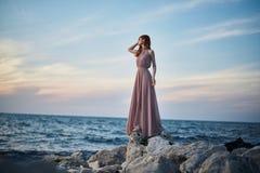 一件长的礼服的美丽的少妇在海站立 免版税库存照片
