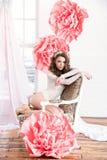 一件长的礼服的美丽的性感的女孩有坐由窗口的巨大的桃红色花的 免版税库存图片