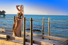 一件长的礼服的年轻美丽的妇女在手上花费与一朵白色玫瑰在海的木路 库存照片