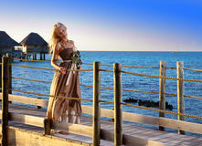 一件长的礼服的年轻美丽的妇女在手上花费与一朵白色玫瑰 免版税库存照片