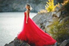 一件长的红色礼服的白肤金发的女孩在自然 免版税库存图片