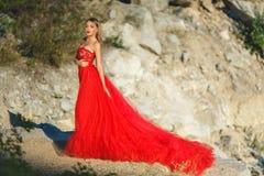 一件长的红色礼服的白肤金发的女孩在自然 免版税库存照片