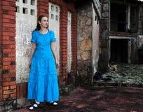 一件长的蓝色礼服的少妇在大厦的老被毁坏的石墙附近站立 免版税图库摄影