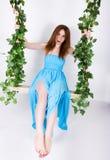 一件长的蓝色礼服的美丽的年轻腿长的红发妇女在摇摆,木摇摆从绳索大麻,绳索暂停了 图库摄影