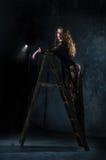 一件长的黑礼服的一个可爱的少妇在梯子,一架梯子站立对难看的东西墙壁 免版税库存照片