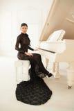 一件长的黑礼服的美丽的女孩 免版税库存照片