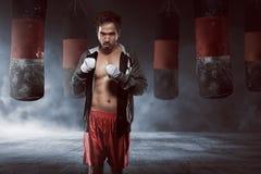 一件黑长袍的年轻亚裔拳击手人有沙袋的 库存照片