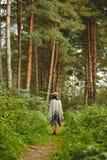 一件雨披和一个帽子的一个女孩在森林里 免版税库存图片