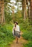 一件雨披和一个帽子的一个女孩在森林里 库存图片