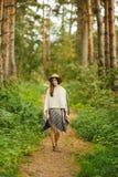 一件雨披和一个帽子的一个女孩在森林里 库存照片