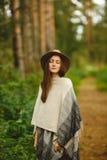 一件雨披和一个帽子的一个女孩在森林里 免版税库存照片