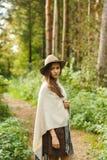 一件雨披和一个帽子的一个女孩在森林里 免版税图库摄影
