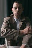 一件雨衣和玻璃的一个孤独的英俊的人用不同的心情 免版税库存照片