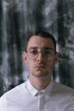 一件雨衣和玻璃的一个孤独的英俊的人用不同的心情 库存图片