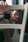 一件雨衣和玻璃的一个孤独的英俊的人用不同的心情 免版税库存图片