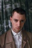 一件雨衣和玻璃的一个孤独的英俊的人用不同的心情 库存照片